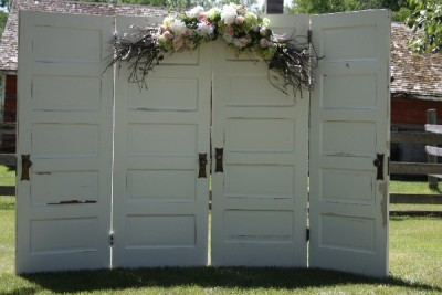 White farmhouse door backdrop with customized florals available for rent