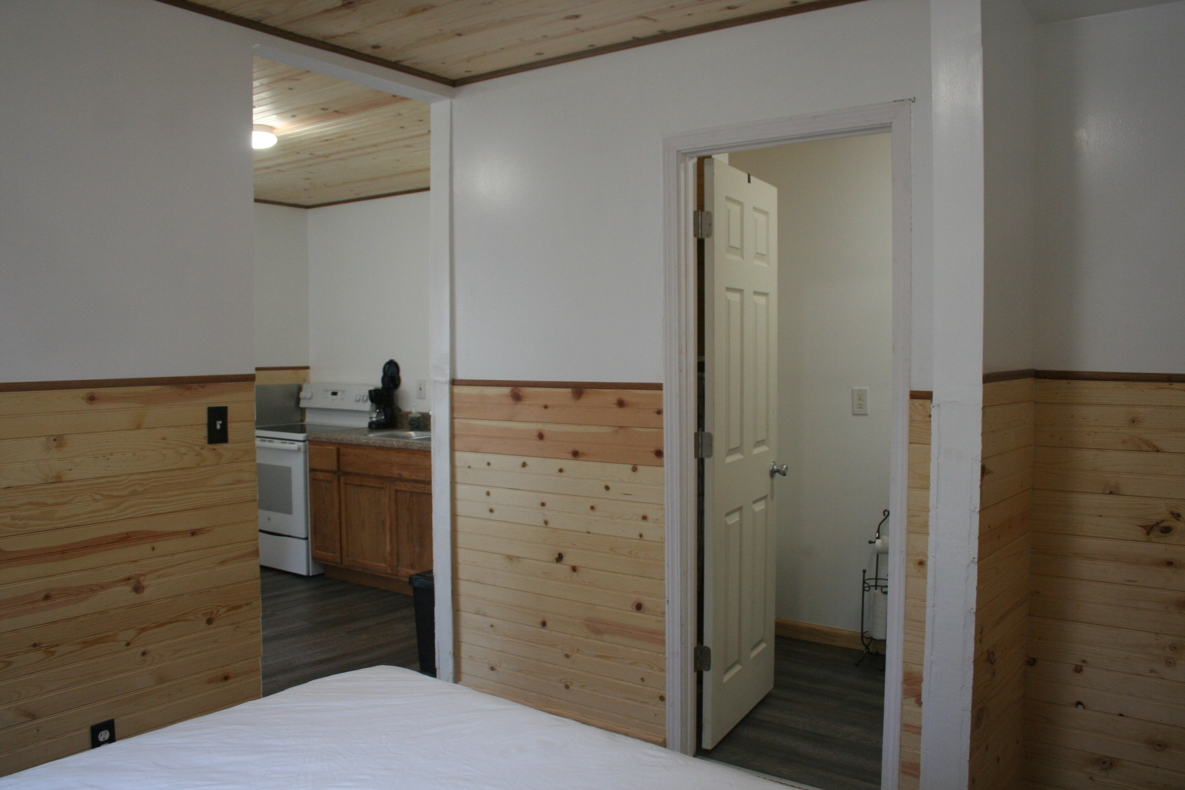 Bedroom looking into bath and kitchen in Cabin #2