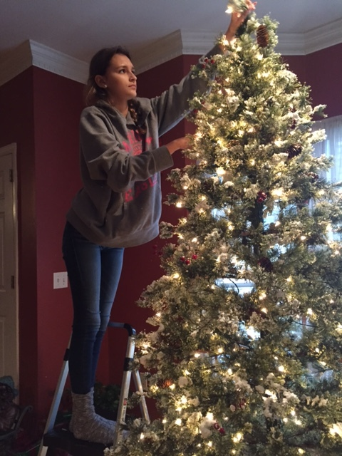 Students at East Hamilton decorate a Christmas tree for the holidays.
