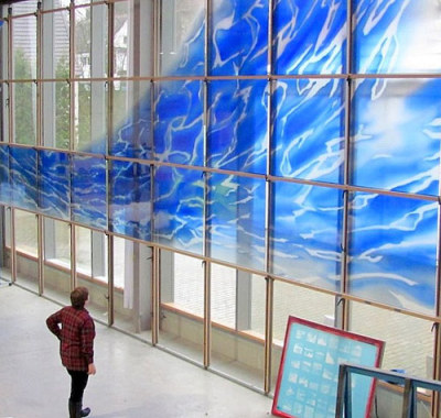artist looks at glass painting in progress on a big easel
