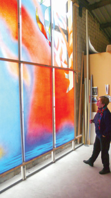 Artist Sarah Hall in the studio looks at stained glass in sunlight