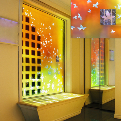 a window with floating maple leaves and solar cells at the solar decathlon