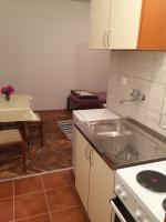 kuhinja i sto sa stolicama u apartmanu