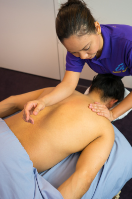 Massage student massaging fellow classmate