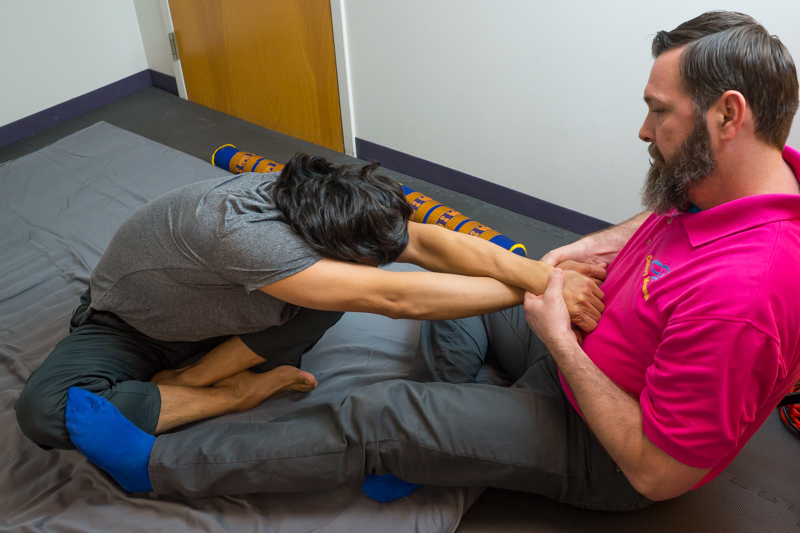 Robert Watts, LMP stretches out a client in the sitting position