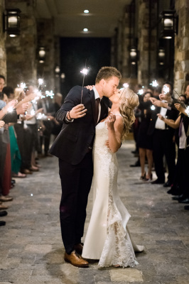 Bride and groom kissing, surrounded by their guests waving sparklers
