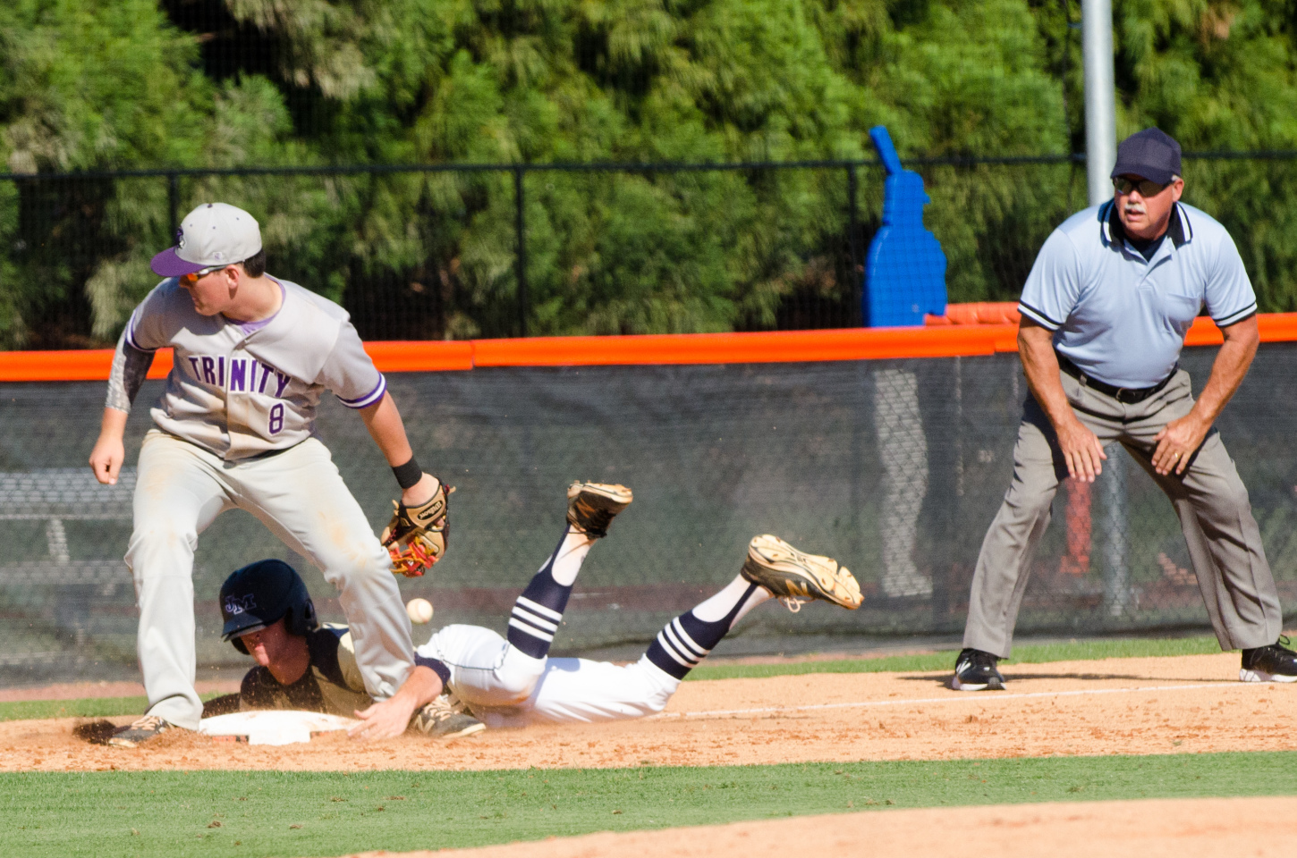 A relay throw to third base gets away from Trinity's Shep Hancock as Tyler Bass slides in safely.