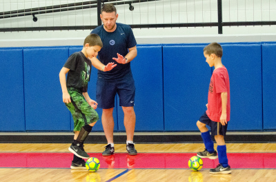 Alan Ewing works with a pair of campers during a drill at this week's Futsal camp.