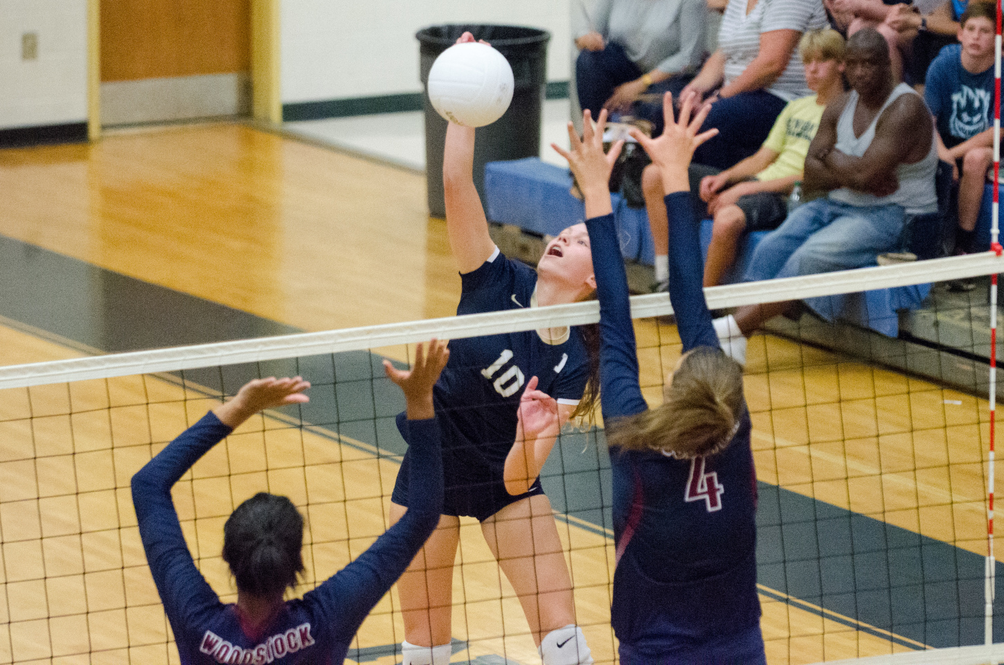 Mary Beth Headley powers a swing in between a pair of Woodstock defenders for a kill.