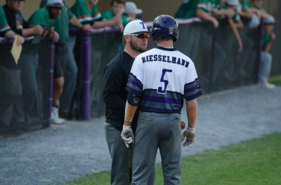 Trinity head coach Blake Austin talks with Kyle Riesselmann during an at bat that led to a home run.