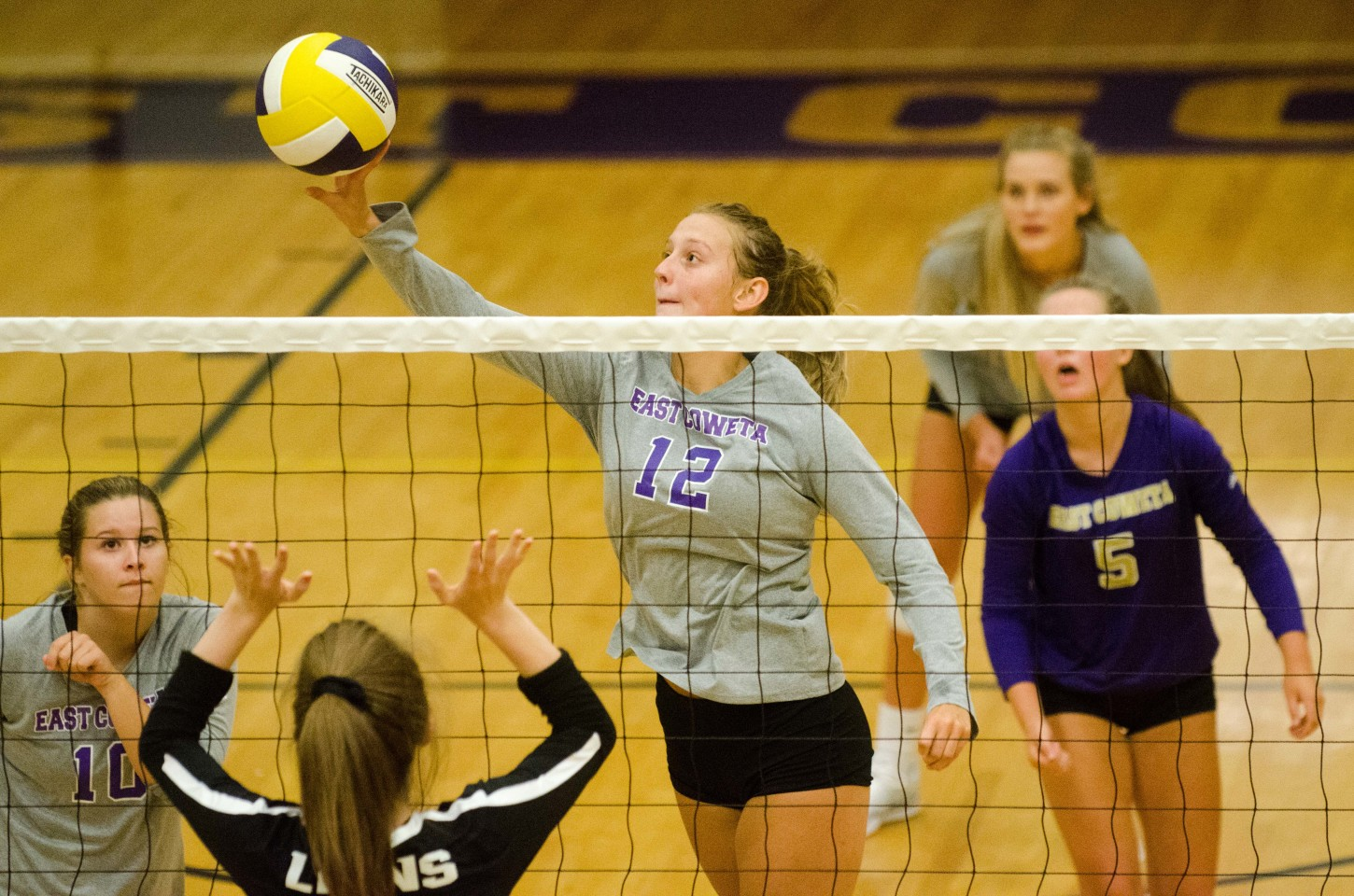East Coweta junior middle hitter Maddie Stewart pushes the ball out of reach of Trinity's front line