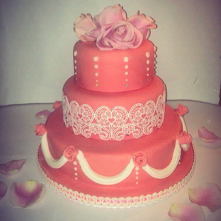 Three tiered wedding cake with lace accents and real roses.