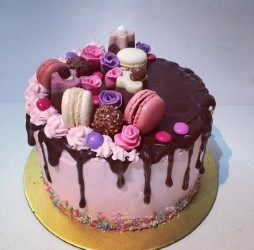 drip cake with macaroons and assorted chocolate toppers.