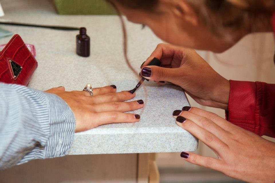 Nail technician touching up a smudged nail before wedding