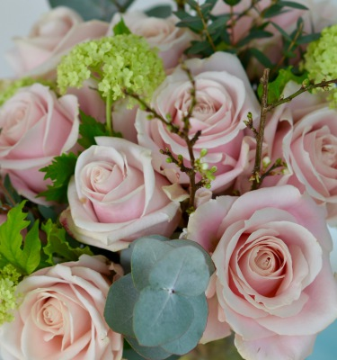 Dreamy pale pink roses, guelder rose and eucalyptus in this classic bouquet.