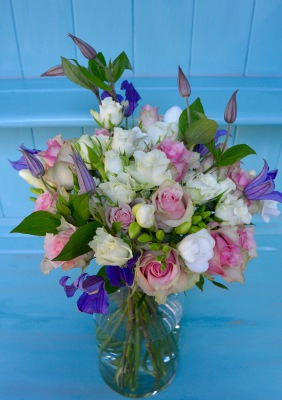 Bouquet of seasonal Spring flowers including roses, freesia and clematis.