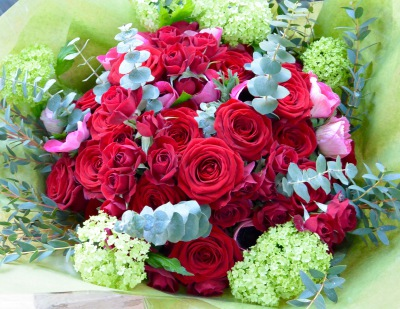 Luxury bouquet of red roses, anemones, guelder roses and fragrant eucalyptus.