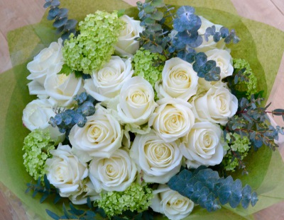 Hand tied bouquet of white roses, guelder rose and eucalyptus