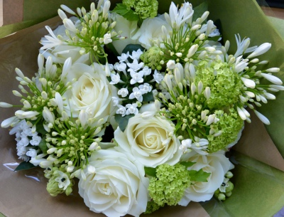 White roses, white agapanthus and guelder rose in this elegant bouquet.