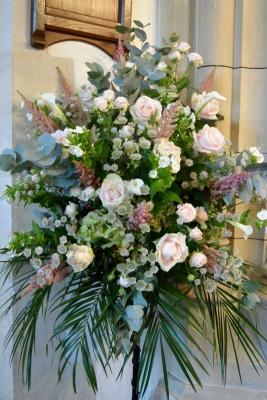Church wedding pedestal arrangement in pinks and greens.