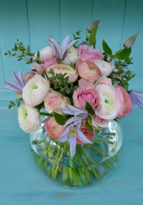 Spring wedding table centre of roses, ranunculus and clematis in glass fishbowl.