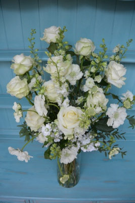 Luxury white wedding flowers including Avalanche roses in a tall glass vase.