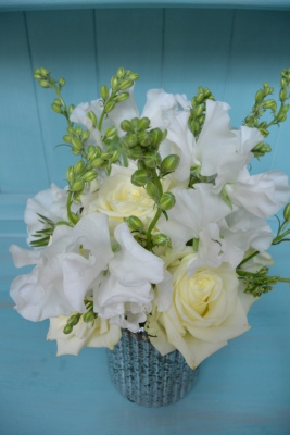 White perfumed garden roses and fragrant sweet peas in a silver glass vase.