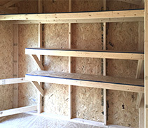 Customized small shelves, workbench and tool storage for a shed.