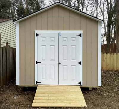 A 10x14x9.5 Potomac style storage shed in LP SmartSide® primed in tan with white fiberglass doors and white trim.