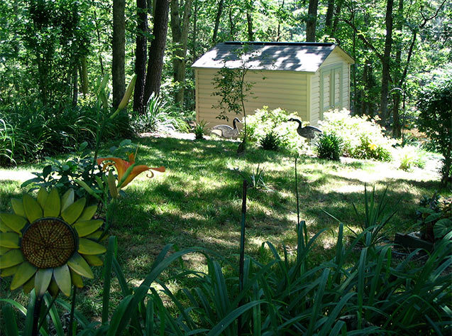 8x10x8 vinyl siding shed in a beautiful garden setting.