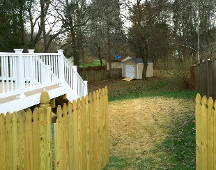 Long view of a 10x14x9.5 riding lawnmower storage shed with fiberglass doors.