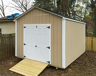 Side view of a 10x14x9.5 riding lawnmower storage shed with fiberglass doors.
