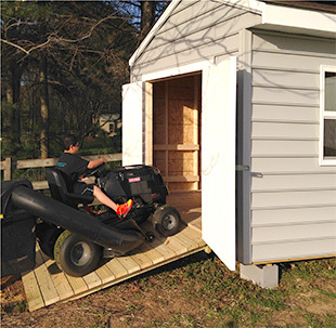Son riding a lawn mower into shed for the first time.
