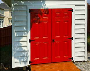 Close up of fiberglass shed doors painted Farmhouse Red.