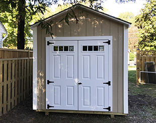 Back and side view of a storage shed to be used as a backboard for playing basketball.