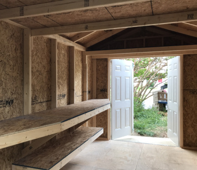 Customized shelves and wrap-a-round workbench for a shed with an upgraded interior.