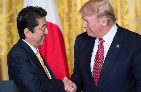 Japan's Prime Minister Shinzo Abe (L) and US President Donald Trump shake hands after a press confer