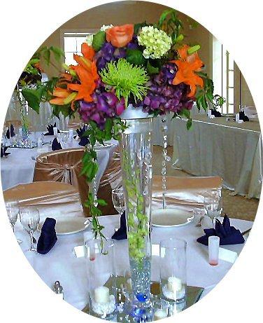 Purple hydrangeas, green spiders, and orange asiatics atop trumpet vase.