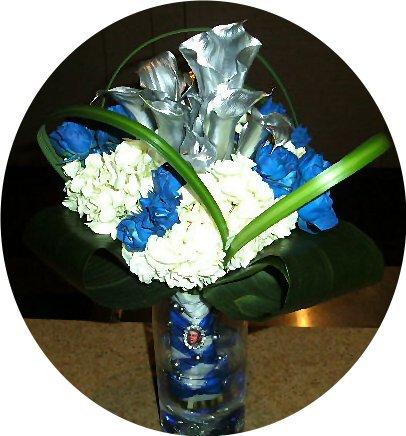 White hydrangeas, royal blue spray roses, and silver mini calla lilies.