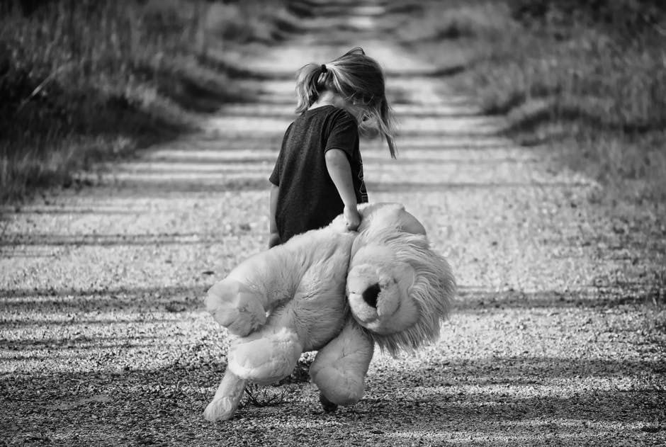 child carrying teddy bear