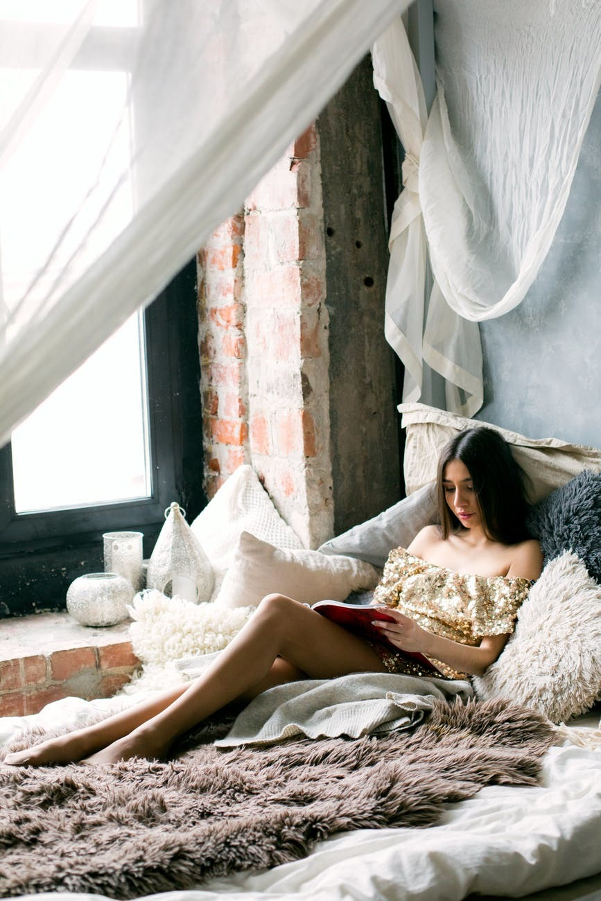 woman laying in bed reading a book