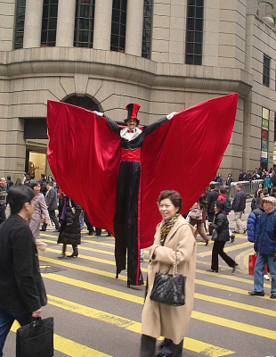 CLASSY WITH RED CAPE ON STILTS