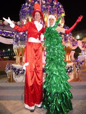 SANTA SUIT & CHRISTMAS DRESS COUPLE ON STILTS
