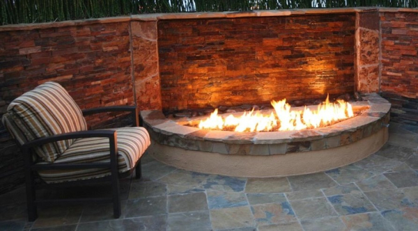 Custom cut crossfire brass burner by warming trends in a unique outdoor firepit