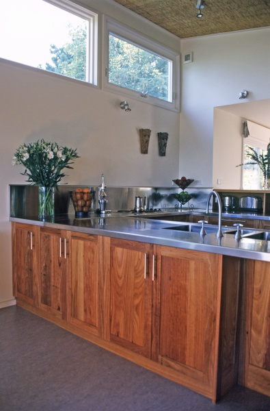 Cornish Hill House designed by sustainable architect Green Point Design. Modern passive solar. Recycled timber and stainless steel kitchen with straw lined ceilings and linoleum floor.