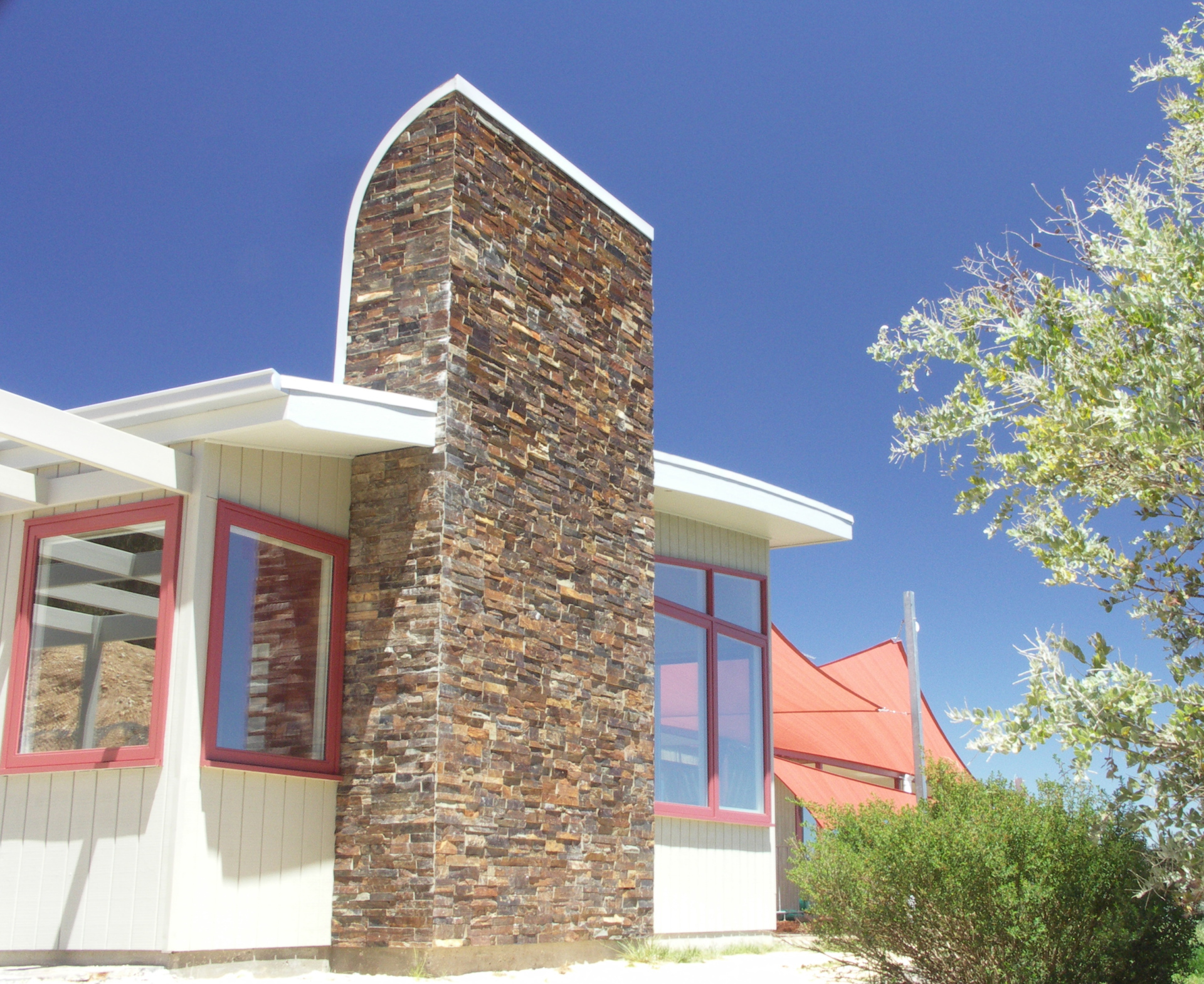 Hepburn House designed by sustainable architect Green Point Design. Stone-clad chimney feature.