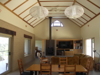 Lavers Hill House designed by sustainable architect Green Point Design.North-facing living room with mudbrick wall.