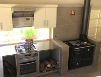 Lavers Hill House designed by sustainable architect Green Point Design. Kitchen with wood-burning stove.
