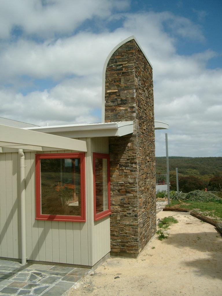 Hepburn House designed by sustainable architect Green Point Design. Stone chimney.