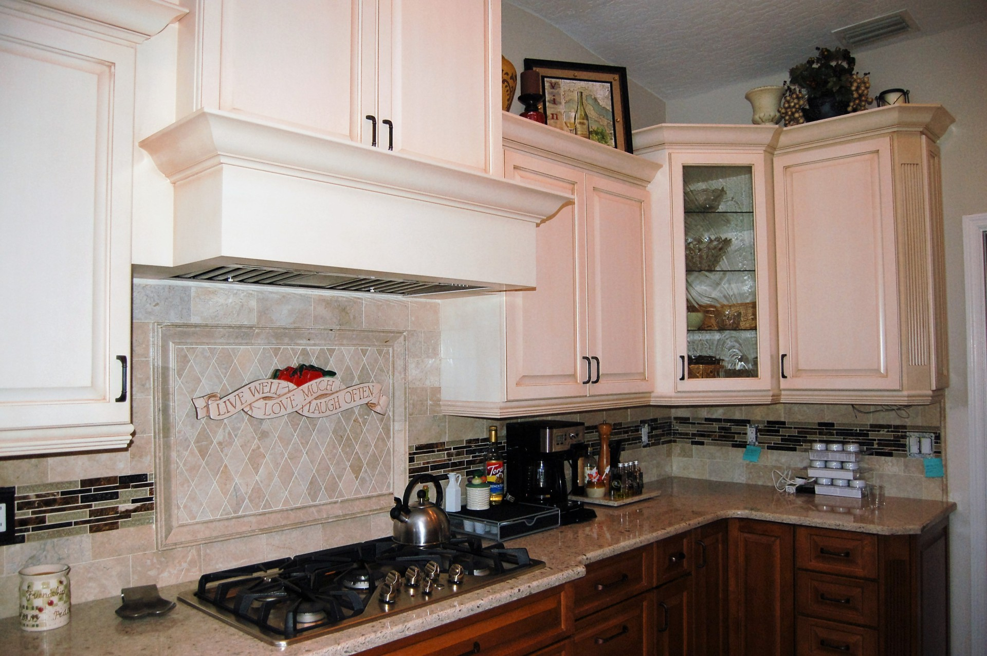 Cream cabinets, tile back splash, travertine back splash, tuscan style kitchen, 2 toned kitchen, crown modeling, fluted trim